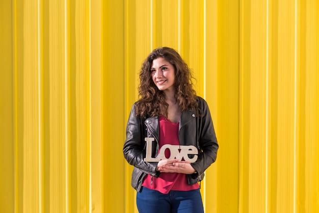 黄色の上の愛の言葉を保持している幸せな美しい若い女性の肖像画。カジュアルウェア。楽しさとライフスタイル。