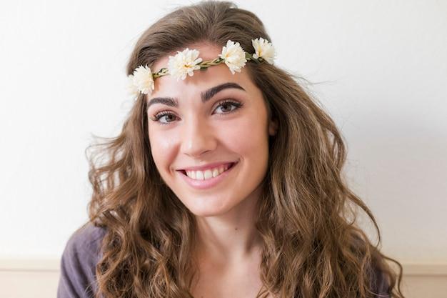 花の花輪を着ている若い美しい女性の肖像画。彼女は屋内で笑っています。ライフスタイル。水平ビュー