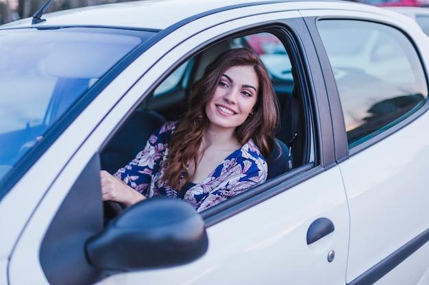 Молодая женщина за рулем автомобиля в городе. портрет красивой женщины в машине, глядя в окно и улыбается. концепции путешествий и отдыха