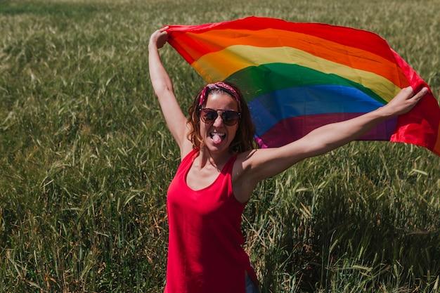 屋外の緑の牧草地にゲイレインボーフラグを保持している女性。同性カップルのための幸福、自由、愛の概念。ライフスタイルアウトドア
