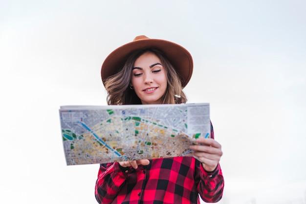 地図を見て、カジュアルな服を着ている若い美しい女性の肖像画を間近します。