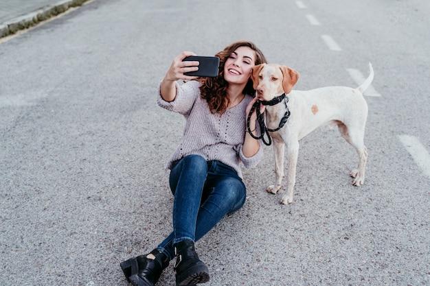 Молодая женщина, принимая селфи с мобильным телефоном со своей собакой на улице