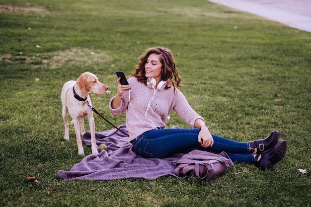 公園で彼女の犬を持つ若い女性。携帯電話を使用しての女性