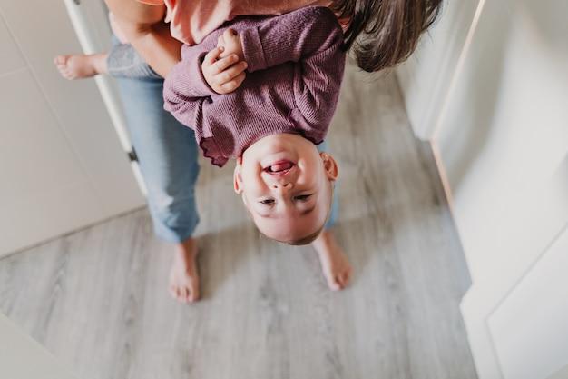 Молодая мать дома играя с ее прелестной годовалой девочкой.