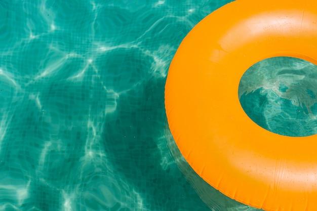 スイミングプールで青い水にオレンジ色のインフレータブルドーナツ