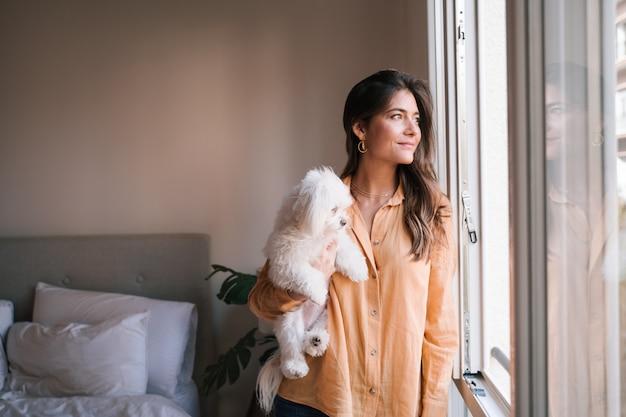 彼女のかわいいマルチーズ犬と一緒に自宅で若い女性