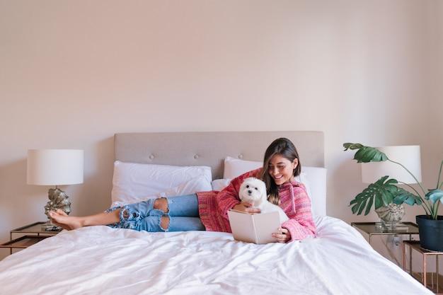 Молодая красивая женщина, читая книгу на кровати у себя дома. симпатичная мальтийская собака. концепция любви к животным