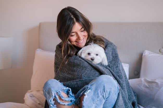 Женщина на кровати у себя дома, завернутая в одеяло со своей милой мальтийской собакой