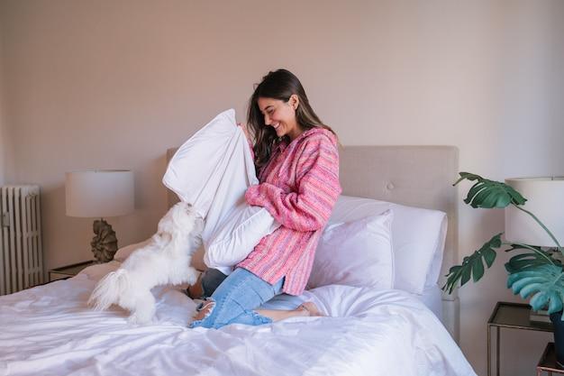 Красивая женщина играет дома со своей милой мальтийской собакой
