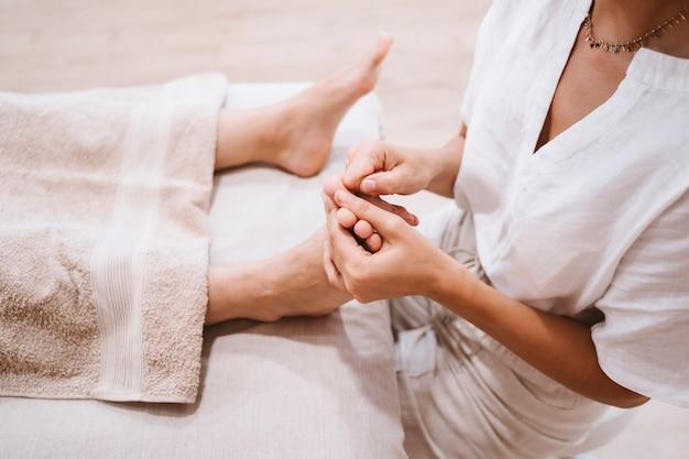 理学療法士クリニックで女性患者に足裏マッサージを与える女性