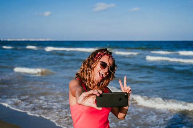 若い女性がビーチで携帯電話で写真を撮る