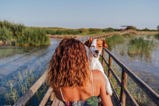 Молодая женщина, держащая ее милый маленький джек рассел терьер на плече. стоя в деревянной пристани в природном парке. туризм, путешествия и концепция любви к животным