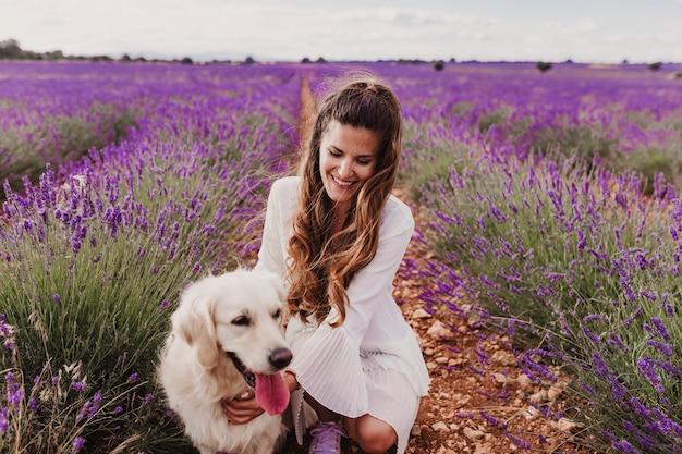 夕暮れ時のラベンダー畑で彼女のゴールデンレトリーバー犬と美しい女性。