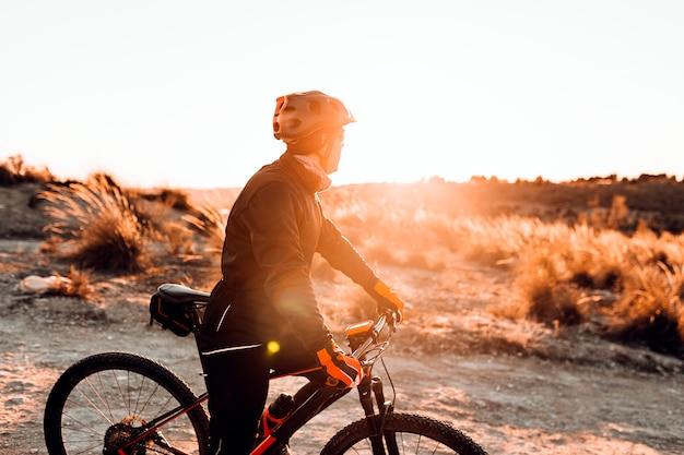 Велосипедист езда на велосипеде вниз скалистом холме на закате. концепция экстремального спорта.