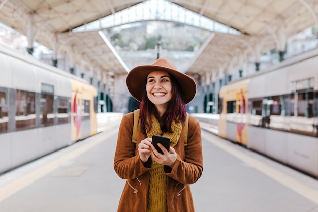 電車に乗って旅行を待っている駅で若い観光客の女性。携帯電話を使用して笑顔