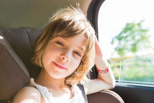 かわいい小さな子供、ブロンドの女の子、幸せなシートベルトを着ている車の座席で、道路の道に行くつもりです、太陽のまぶしさを反映