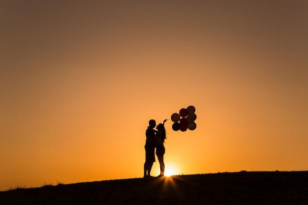 Силуэт пара играет с воздушными шарами на закате