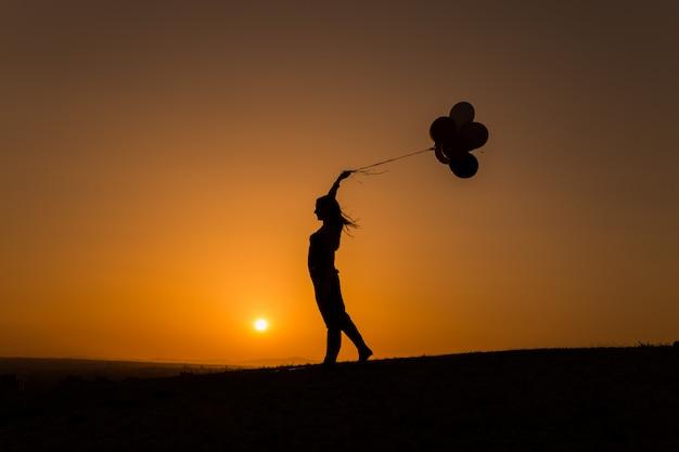 Силуэт молодой женщины, играющей с воздушными шарами на закате