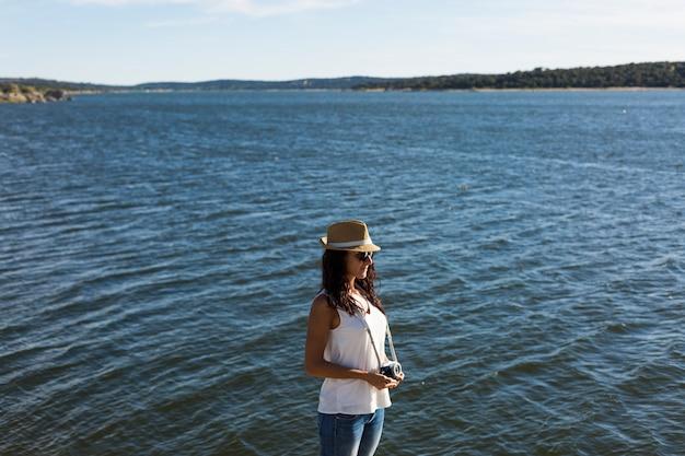 カメラを保持してビーチで美しい若い女性。日没。夏とライフスタイル