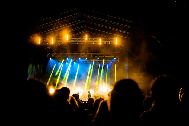 Изображение большого количества людей, наслаждающихся ночным представлением, большой неузнаваемой толпой, танцующей с поднятыми вверх руками и мобильными телефонами на концерте. ночная жизнь