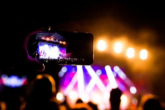 夜のパフォーマンス、盛り上がった手とコンサートで携帯電話で踊る認識できない大群衆を楽しんでいる多くの人々の写真。ナイトライフ