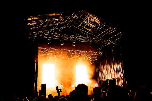 夜のパフォーマンス、盛り上がった手とコンサートで携帯電話で踊る認識できない大群衆を楽しんでいる多くの人々の写真。ナイトライフ。ミュージシャンや歌手のシルエット