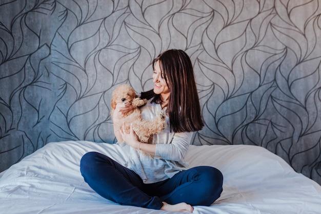 Портрет милого коричневого пуделя игрушки с его владельцем молодой женщины дома, дневное время, внутри помещения.