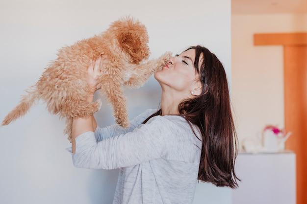 Женщина, держащая ребенка игрушка пудель высоко. дом, в помещении, любовь и забота о животных концепции
