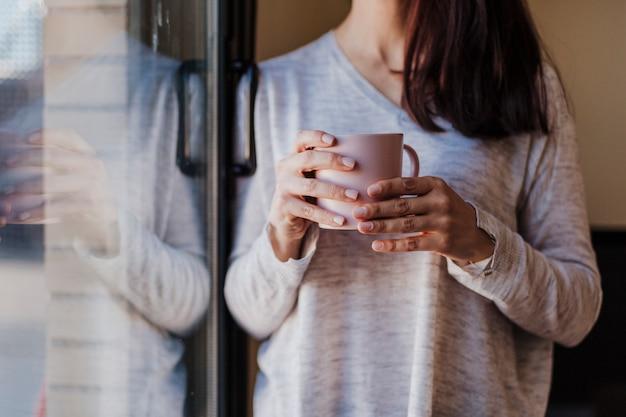 認識できない美しい若い女性が家の窓際に座ってコーヒーを飲みます。