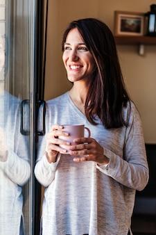 家の窓際に座ってコーヒーを飲んで美しい若い女性。