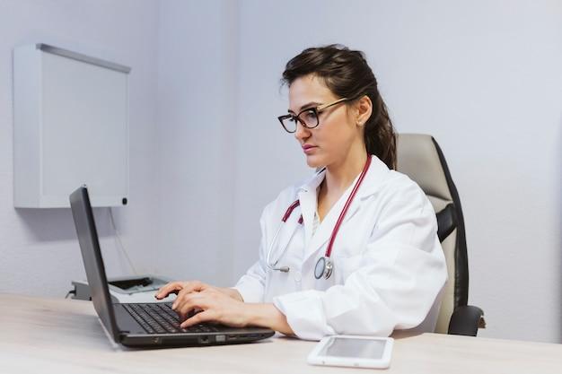 若い医者は相談でラップトップに取り組んでいる女性。屋内での現代医療コンセプト