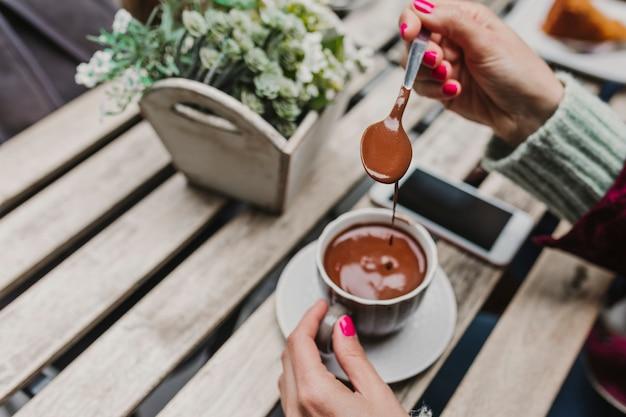 Молодая неузнаваемая кавказская женщина наслаждается горячим шоколадом на террасе с друзьями