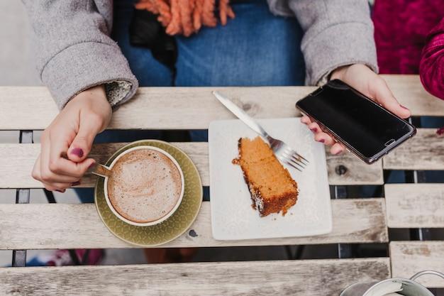 Молодая неузнаваемая кавказская женщина наслаждается чашечкой кофе и куском пирога на террасе с друзьями