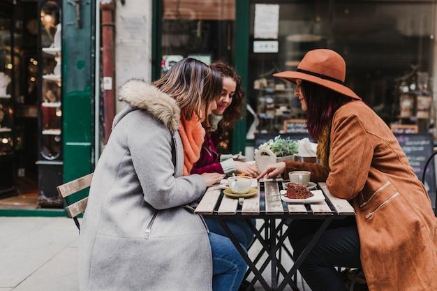 Три подруги, имеющие кофе на террасе в порту, португалия. веселый разговор