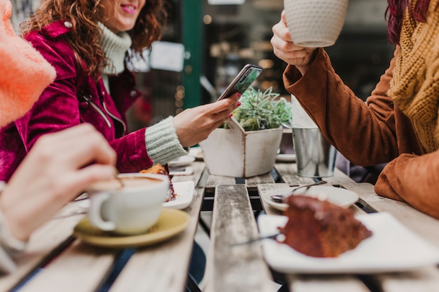 Три неузнаваемых подруги-женщины пьют кофе на террасе в порту, португалия. веселый разговор