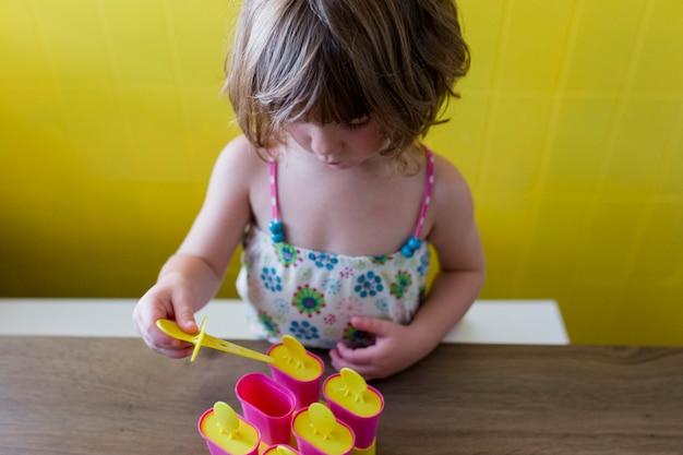 Портрет молодой красивой девушки ребенк играя с мороженым дома. счастье и образ жизни в помещении. летом. желтая стена