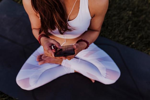 До неузнаваемости азиатская женщина расслабилась после практики йоги, слушая музыку на наушники и мобильный телефон.