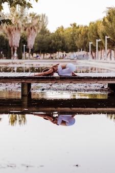 Молодая красивая азиатская женщина делая йогу в парке. сидеть на мосту с отражением на воде озера. йога и концепция здорового образа жизни