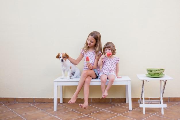 Две красивые сестры дети едят арбузное мороженое со своей милой собакой. семейная любовь и стиль жизни на природе