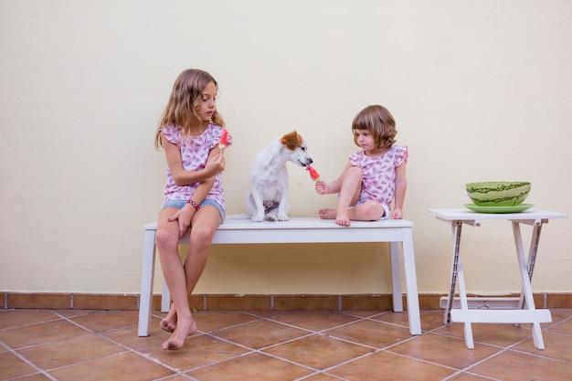 Две красивые сестры дети едят арбузное мороженое. семейная любовь и стиль жизни на природе