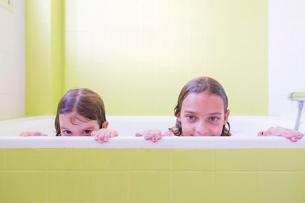泡の泡で遊んで風呂に入って幸せな笑い姉妹子供。バスタブの小さな子供たち。屋内での家族のライフスタイル