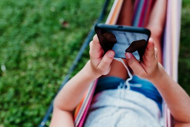 Непознаваемая девушка подростка лежа на красочном гамаке на саде. слушая музыку на мобильном телефоне и гарнитуру и улыбаясь. отдыхать и веселиться на свежем воздухе