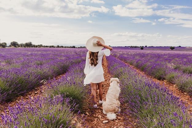 ラベンダー畑で彼女の犬を持つ女性