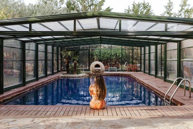 Красивая молодая женщина расслабиться в крытом бассейне. летнее время и образ жизни