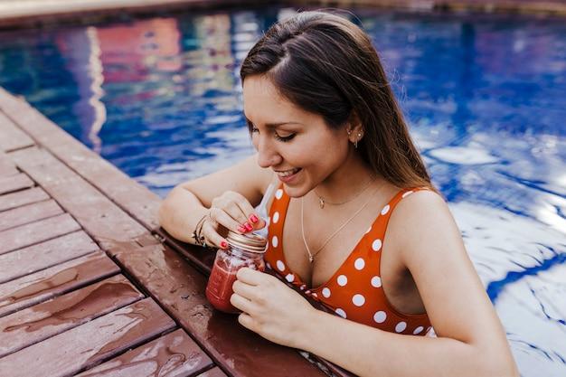 Красивая молодая женщина отдыха у бассейна. держа здоровый сок и отдыхая летнее время и образ жизни