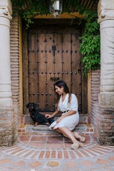 自宅で彼女の所有者と屋外に座っているかわいい小さなソーセージ犬。彼女の犬を抱きしめる女性。動物のコンセプトが大好き