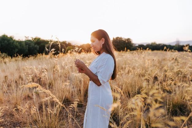 黄色のフィールドで夕暮れ時の屋外で若い美しい白人女性の肖像画。幸福とライフスタイル