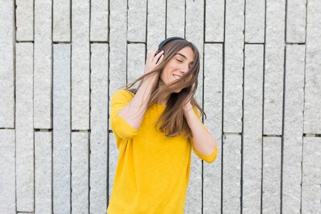 Портрет красивой молодой женщины слушая к музыке на наушниках. она танцует, прыгает и улыбается. она носит повседневную одежду. стиль жизни на открытом воздухе