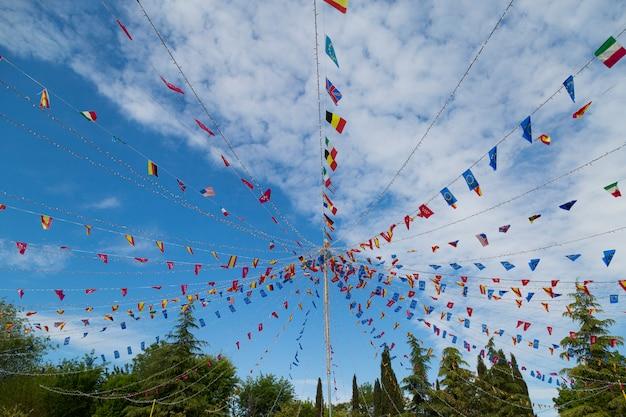 青い空にぶら下がっているカラフルなペナントフラグ。祭りやパーティーのコンセプト