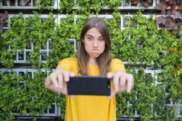 携帯電話で写真を撮ると変な顔を作る美しい若い女性の屋外の肖像画。黄色のカジュアルなシャツを着て、笑顔。
